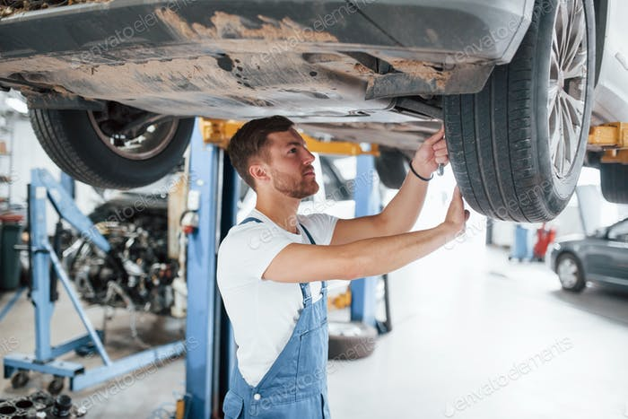 Tightening up some bolts. Employee in the blue colored uniform works in the automobile salon