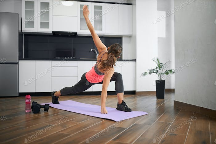 Unrecognizable young woman stretching at home