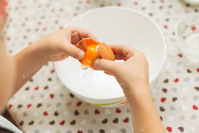 Close-up hands breaking eggs in a bowl