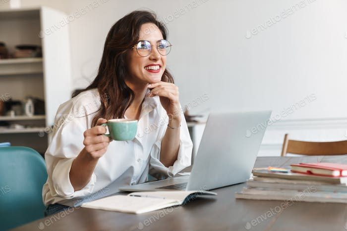 Smiling pretty young brunette woman drinking coffee