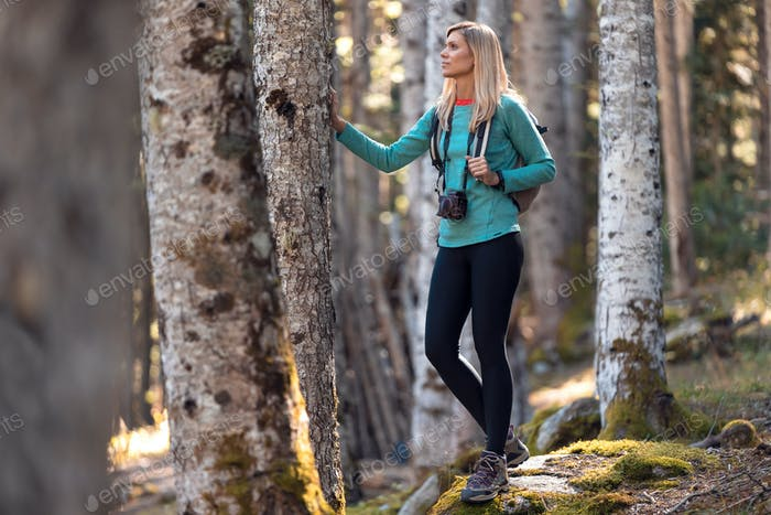 Pretty young woman traveler with backpack looking to the side in the natural forest.