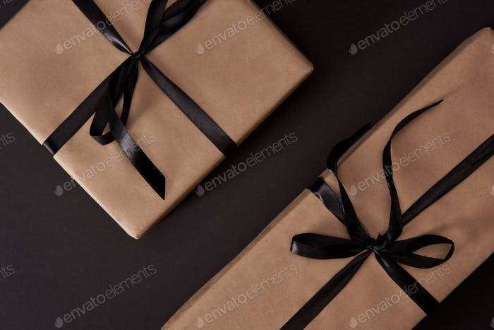 top view of craft wrapped gift boxes on black surface, black friday concept