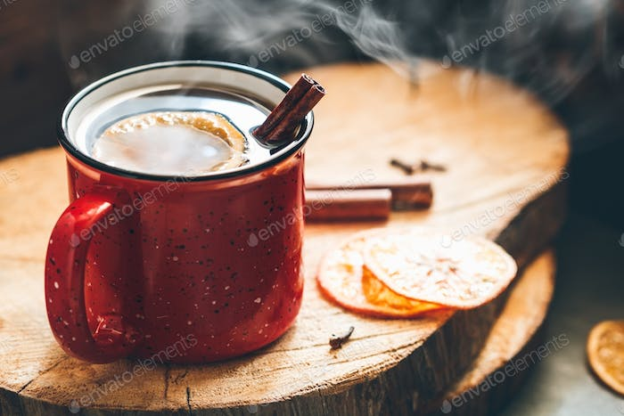Mulled wine in a red ceramic mug over rustic wooden boards surrounded spices.