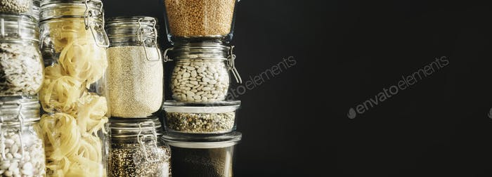 Banner with assortment of grain products and pasta in glass storage containers on wooden table