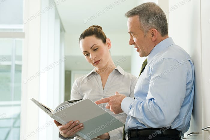 Two business colleagues reading a document