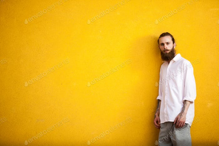 Tattooed fashion bearded hipster on yellow wall