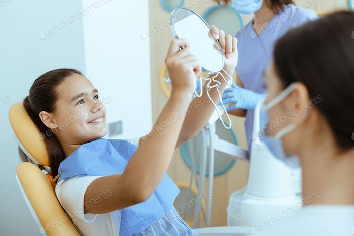 Glückliches Mädchen auf Zahnarztstuhl mit Serviette sieht im Spiegel im Inneren des modernen Büros