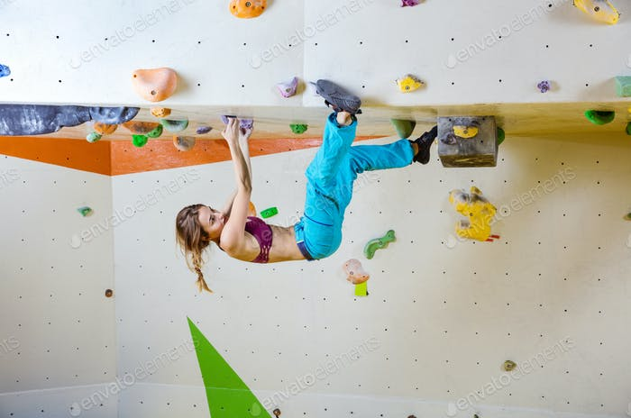 Young woman climbing upside down in bouldering gym