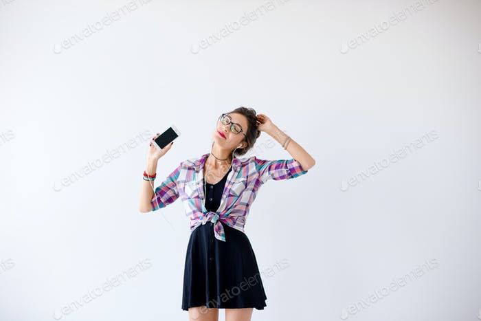Girl in headphones and glasses listening to music and dancing