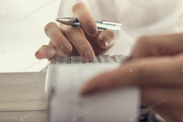 Closeup low angle view of a woman using a manual adding machine