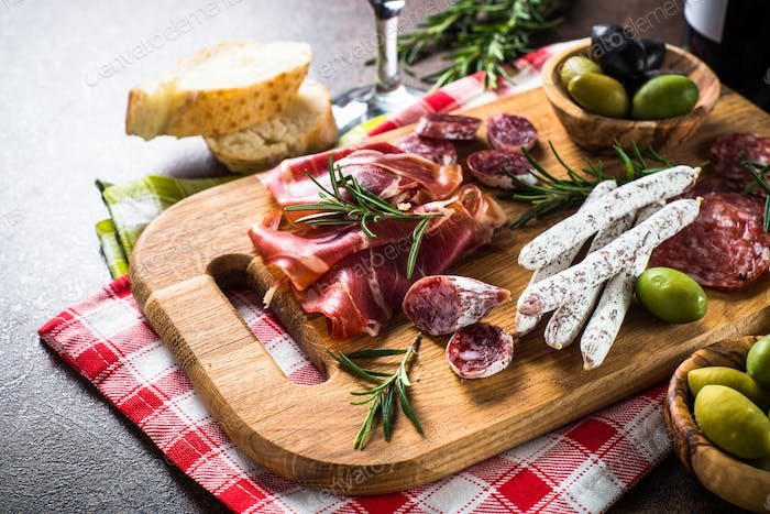Antipasto delicatessen - sliced meat, ham, salami, olives on wooden board