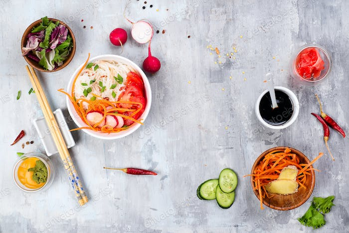 Asian spicy salad of glass noodles or funchoza with carrots and vegetables salad on stone background