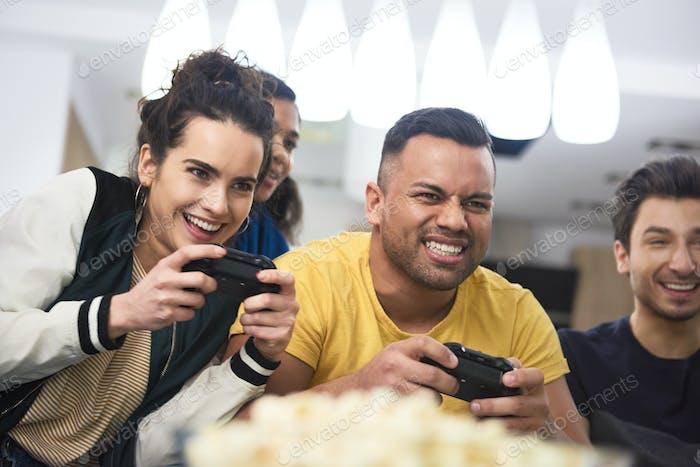 Freunde, die beim Spielen einer Spielkonsole konkurrieren.