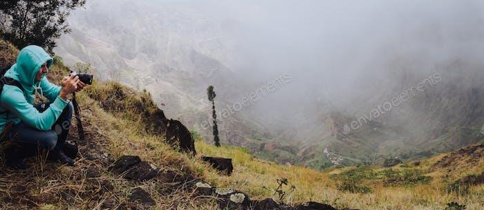 Panoramic shot of traveler making photo of amazing steep mountainous terrain with lush canyon valley