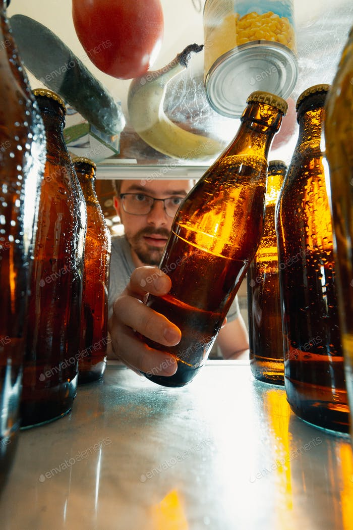 Caucasian man takes cold refreshing beer from out the fridge, inside view from fridge of hand