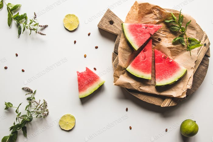 watermelon on a sliced board with mint and slices of lime. food