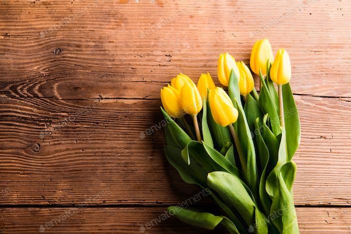 Ramo de tulipanes amarillos sobre Fondo de De madera marrón