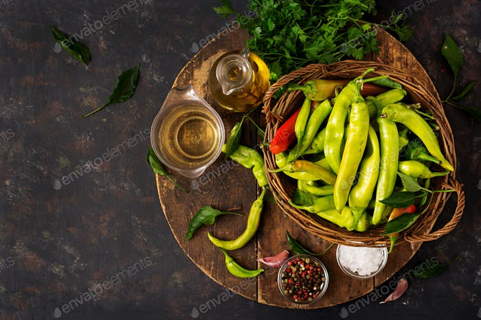 Green chili peppers in a basket on a dark background. Preparation for pickling. Flat lay. Top view