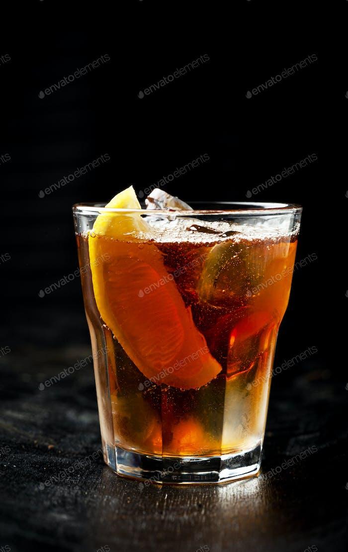 Ice tea with  lemon and ice on a dark