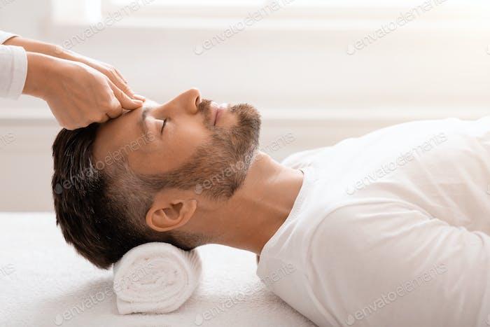 Бородатый мужчина с расслабляющим массажем головы в спа-центре