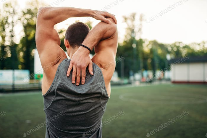 Male athlete doing stretching exercise, back view