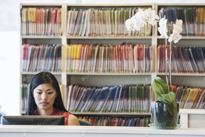 Asian female working in a medical office with file folders in the background