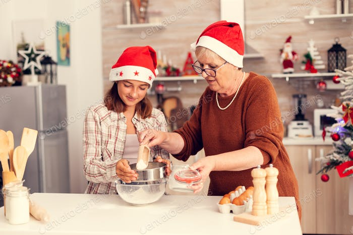 Mature woman and child on christmas day making cookies dough