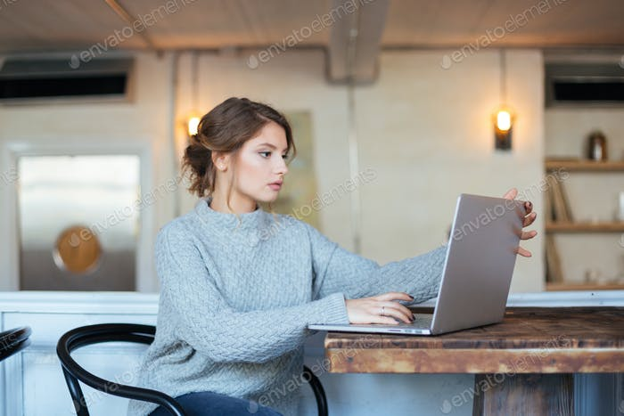 Woman using laptop computer in cafe