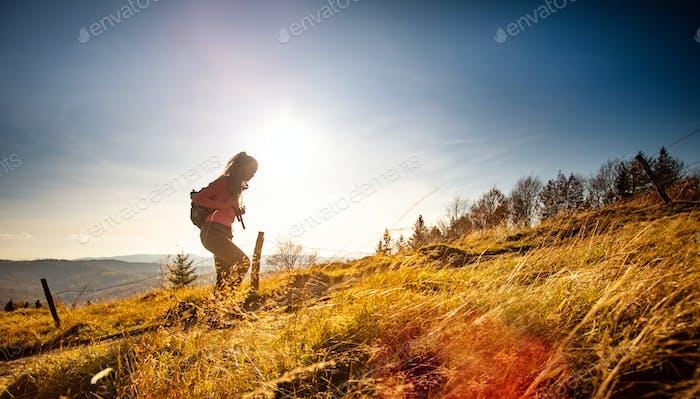 Wanderer junge Frau mit Rucksack steigt auf den Berggipfel auf Berge Landschaftshintergrund