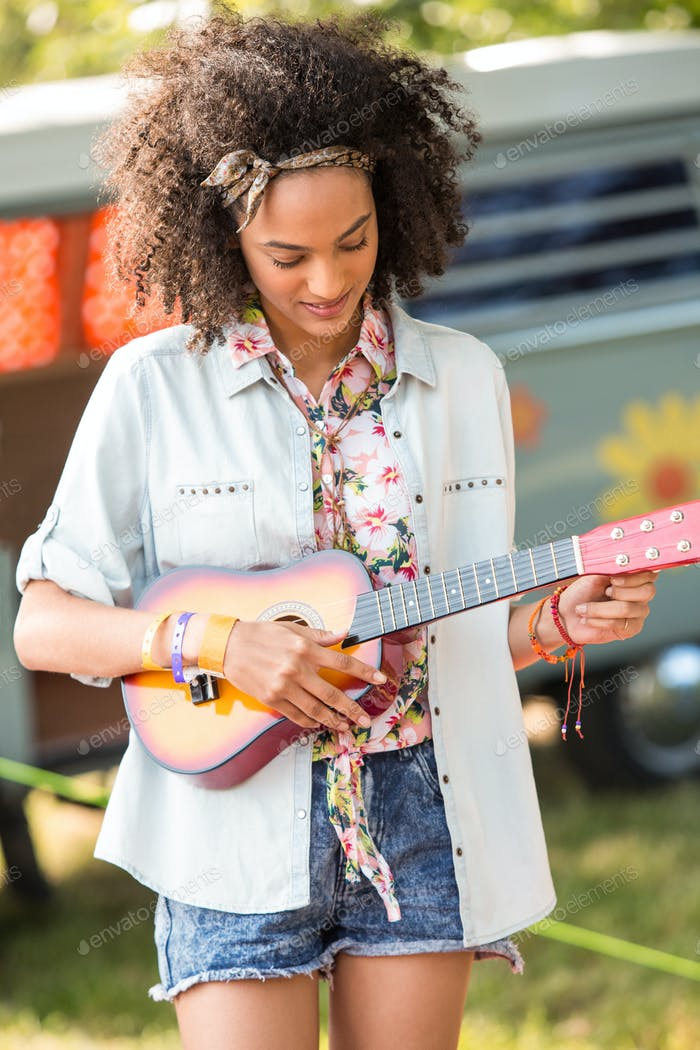Pretty hipster playing the ukulele on a sunny day