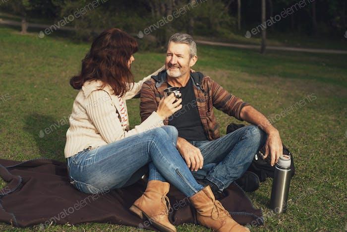 Paar mittleren Alters sitzt auf dem Gras im Park, umarmt und trinkt Tee.