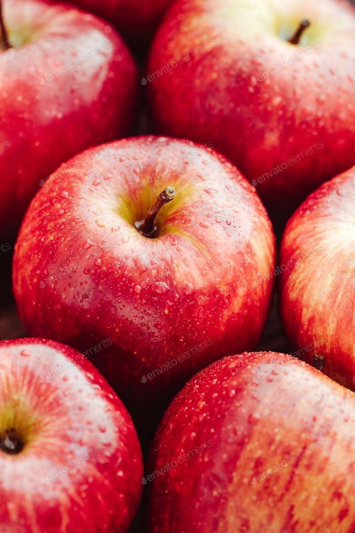 Harvest of ripe apples variety Red Delicious. Food background, macro photography.