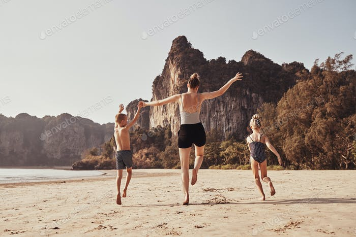 Carefree mother and children running along a sandy beach together