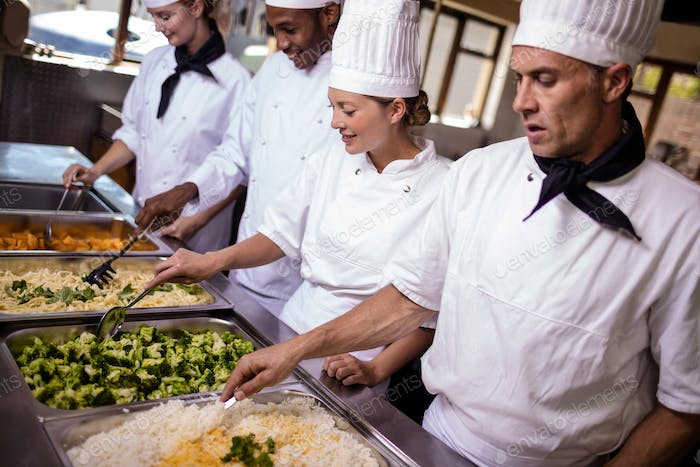 Group of chefs stirring prepard foods in kitchen at hotel