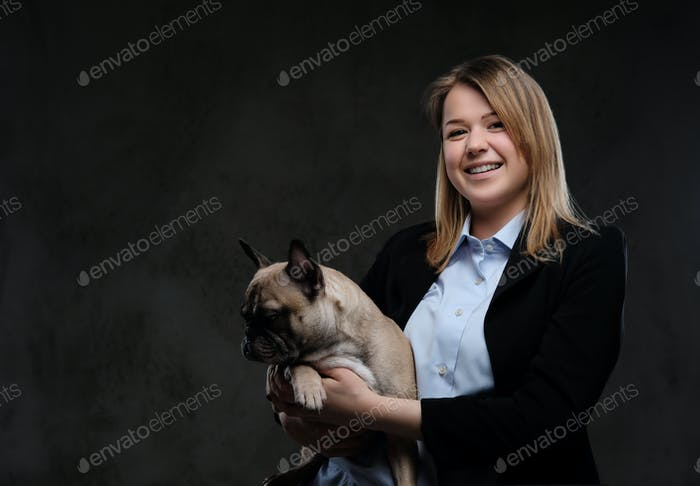 Portrait of a smiling blonde woman breeder holds her cute pug. Isolated on dark textured background.