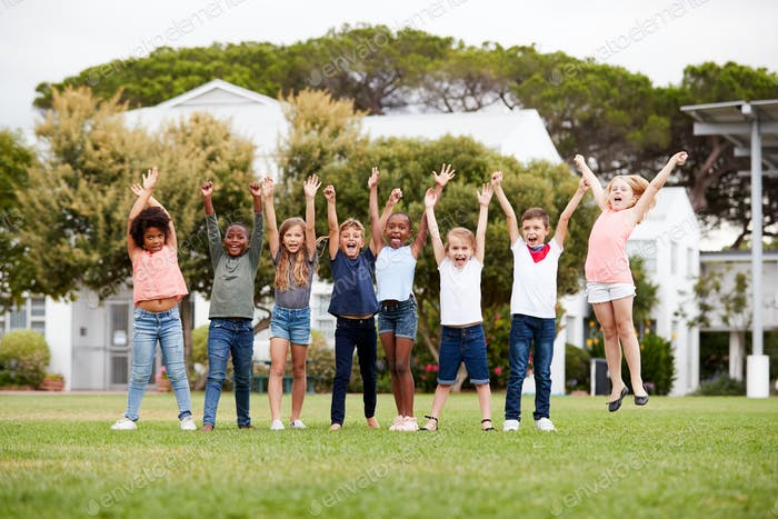 Group Of Excited Elementary School Pupils Standing On Playing Field At Break Time With Arms Raised