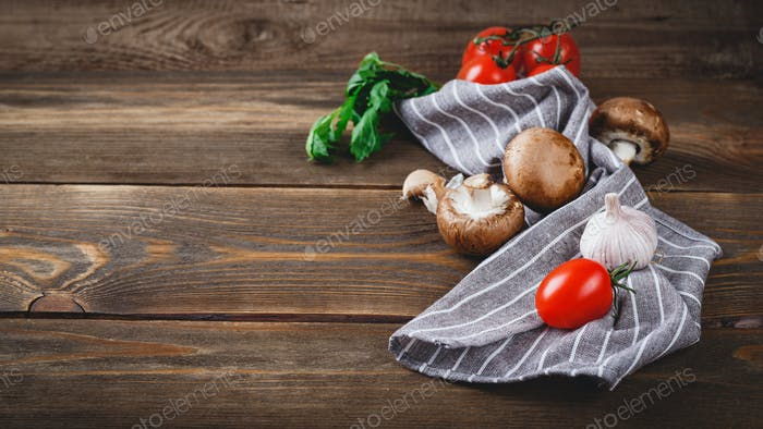Tomatoes, garlic, champignons, parsley, pepper shaker, forks and napkin on wooden background