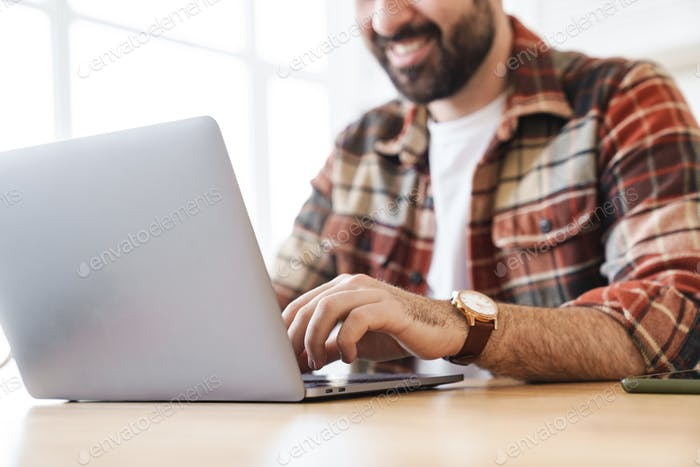 Cropped portrait of cheerful man working with laptop and smiling