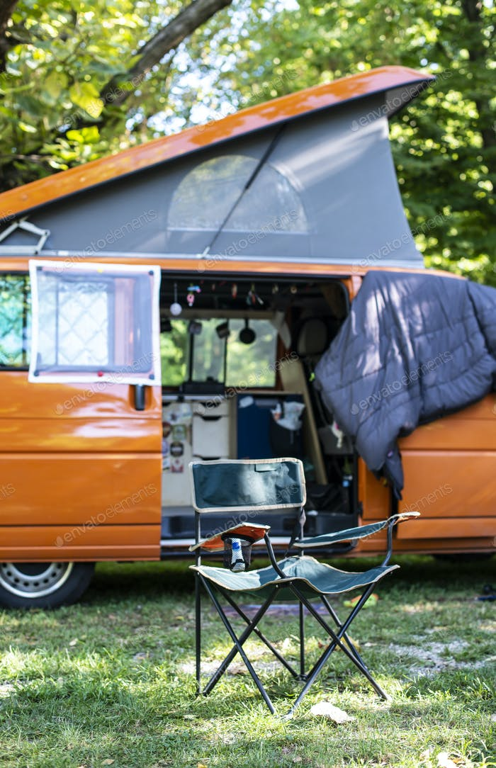 Camper in campsite. Outdoor equipment and travel van on green me