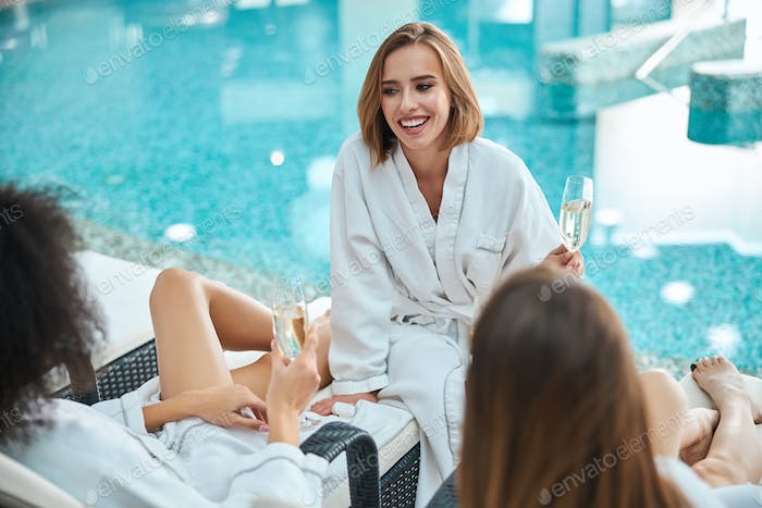 Joyful young woman spending quality time with friends at resort