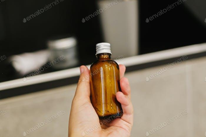 Hand holding ayurveda ubtan powder in glass