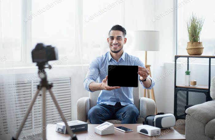 Arab male influencer shooting video review of modern tablet computer on professional dslr camera at
