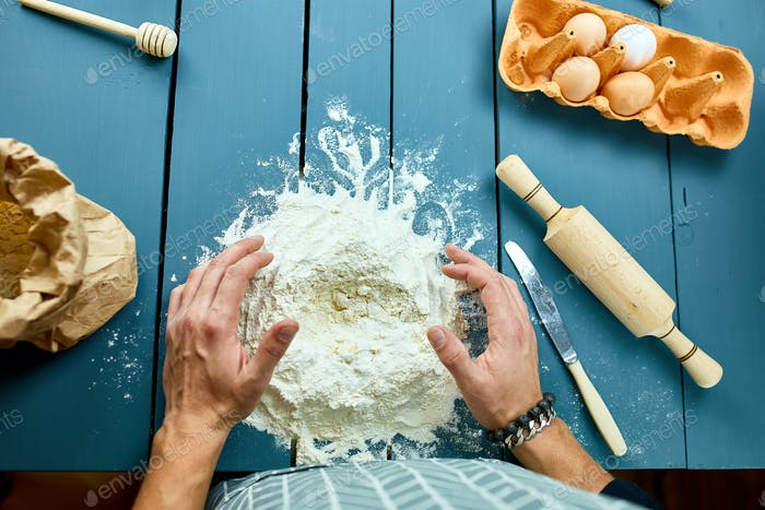 Man forming the dough on a floured surface and kneading it with his hands.