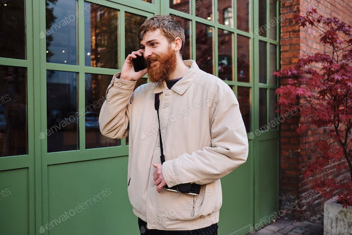 Young positive bearded man happily talking on cellphone on street alone