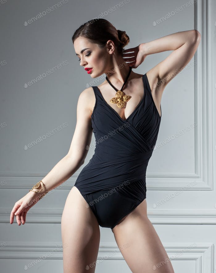 Sexy woman posing in black swimsuit in interior