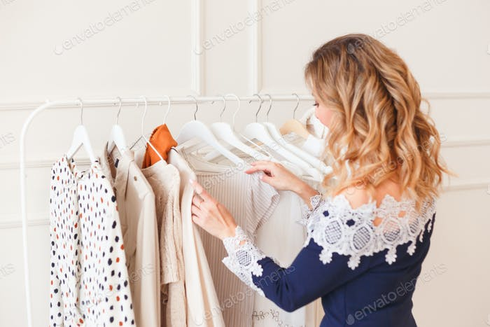Young woman choosing clothes on a rack for the party. Designers shop or own wardrobe