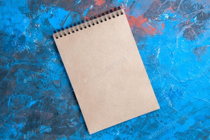Draufsicht eines Notizbuchs auf blauem Hintergrund mit freiem Speicherplatz