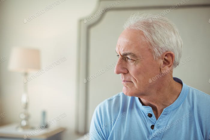 Thoughtful senior man sitting in bed room