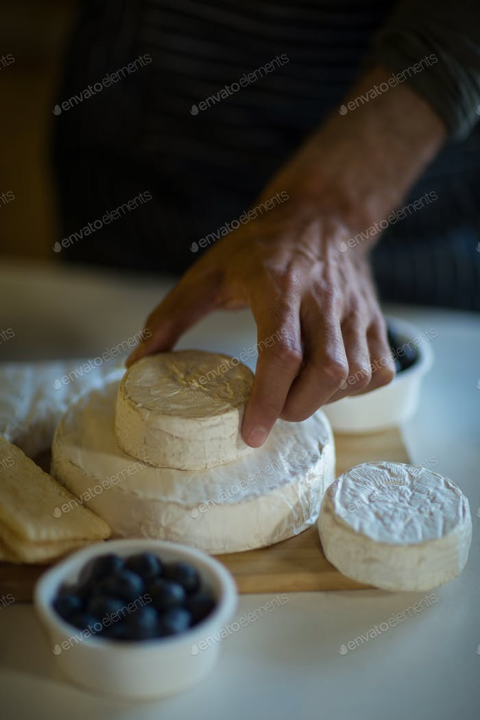 Salesman arranging cheese at counter