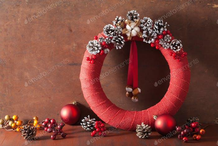 roter Weihnachtskranz auf Holzhintergrund